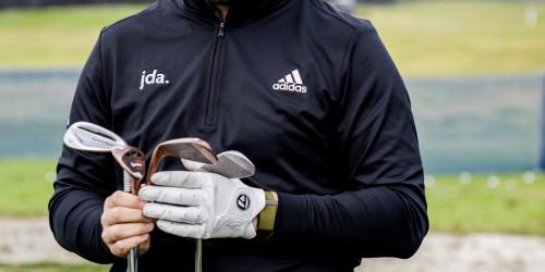 John Rahm looking at TaylorMade golf clubs